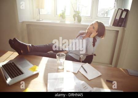 Young business woman sitting at her desk in office with her legs on the desk. Caucasian female relaxing in home - Stock Photo