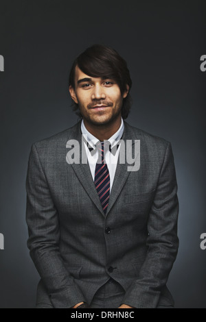 Portrait of smart young male executive looking at camera confidently. Handsome asian businessman against black background. - Stock Photo