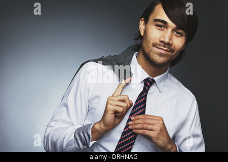 Portrait of handsome male entrepreneur holding his coat over shoulder looking at camera smiling. Asian businessman - Stock Photo