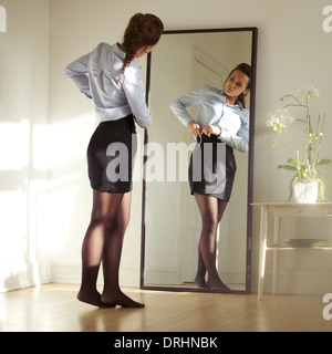 Pretty young businesswoman fixing her skirt in front of mirror. Beautiful caucasian female model getting ready for - Stock Photo