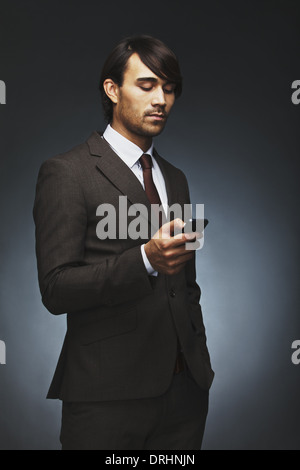 Handsome young businessman reading text message on his smart phone. Mixed race male model in business suit using - Stock Photo