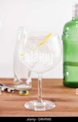 Classic gin tonic in balon glass with a twist of lemon - Stock Photo