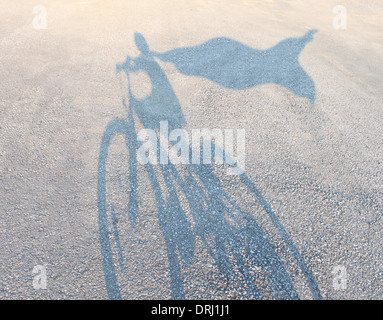 Superhero child wearing a cape riding a bicycle as a cast shadow on a road pretending to be a powerful hero as a - Stock Photo