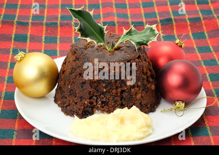 Traditional Christmas pudding with a sprig of holly and brandy butter - studio shot - Stock Photo
