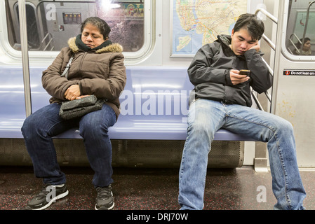 Two passengers riding and sitting on a New York City subway. - Stock Photo