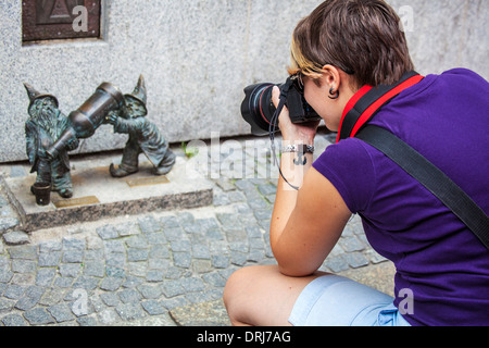 A young tourist takes photographs of Wroclaw's famous little bronze gnomes, dwarfs or krasnale statuettes. - Stock Photo