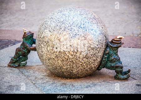 Two of Wroclaw's famous little bronze gnomes, dwarfs or krasnale statuettes. - Stock Photo