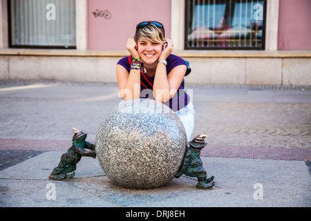 A pretty young tourist poses with Wroclaw's famous little bronze gnomes, dwarfs or krasnale statuettes. - Stock Photo