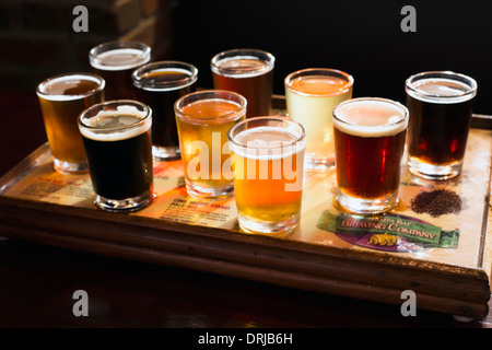 flight of beers for tasting in a brew pub - Stock Photo