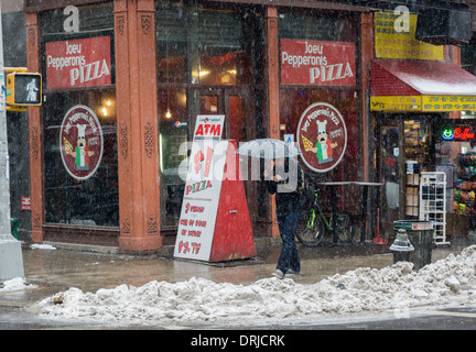 Passer-by outside of Joey Pepperonis Pizza in Chinatown in New York - Stock Photo
