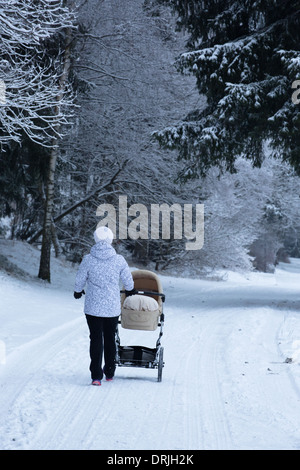 A woman pushes a pram or pushchair in a snowy forest - Stock Photo