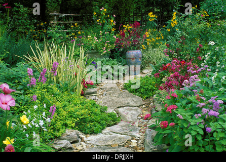 Stone path curves through lush blooming garden where a painted Mexican pot adds interest and color, Missouri USA - Stock Photo