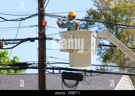 Power engineer in lift bucket working on power lines and adjusting tension, Braintree, Massachusetts, USA - Stock Photo