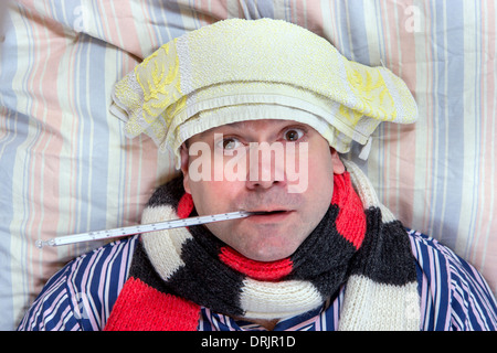 sick man lying in bed - Stock Photo