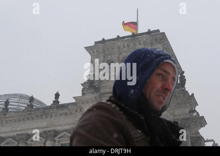 Berlin, Germany. 27th Jan, 2014. A tourist walks past Germany's Reichstag building on which German flag is set half - Stock Photo