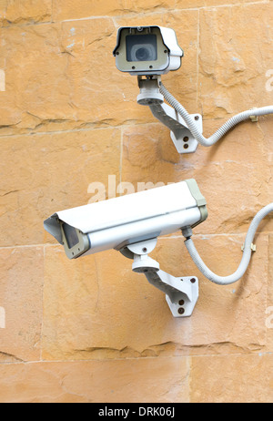 Two CCTV security cameras on the corner of a building. - Stock Photo