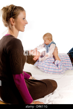 Happy mother watching her husband play with their four months old baby girl - Stock Photo