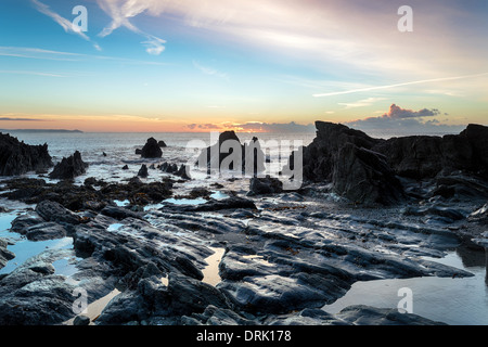 Low tide and sunrise at the beach at Looe in Cornwall - Stock Photo