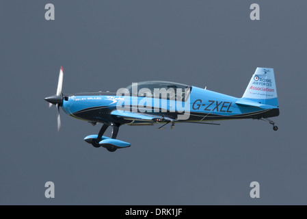 An extra 300s from 'The Blades' aerobatic team landing lit by sunlight but set against a neutral but dark sky background - Stock Photo