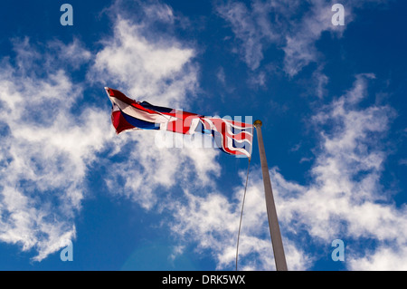 Union Jack flag blowing in wind seen from below - Stock Photo