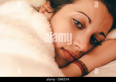 Young woman resting in bed and thinking about something - Stock Photo