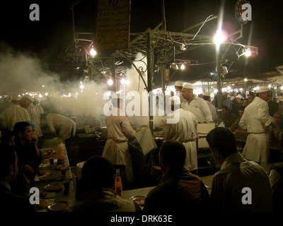 Grill smoke swirls around chefs at open air food stalls in Jemaa el Fna square at night, Marrakesh, Morocco - Stock Photo