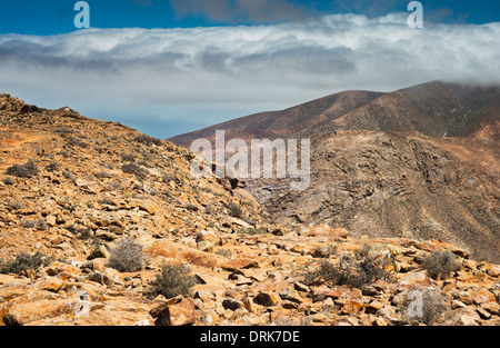 Mountain top composed of intrusive syenite rock at Degollada de los Granadillos, Fuerteventura, with gabbro mountains - Stock Photo