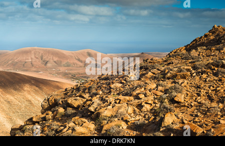 Mountain composed of syenite rock at Degollada de los Granadillos, Fuerteventura, with gabbro and pyroxenite mountains - Stock Photo