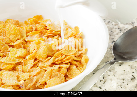 Cornflakes with milk being poured - Stock Photo
