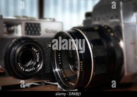 A pair of veteran cameras, a Rollei B35 compact and a Pentax S1a 35mm single lens reflex camera. - Stock Photo