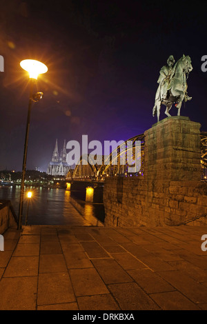 Germany, North Rhine-Westphalia, Cologne, lighted Cologne Cathedral and Hohenzollern Bridge with monument of Wilhelm - Stock Photo