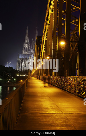 Germany, North Rhine-Westphalia, Cologne, lighted Cologne Cathedral and Hohenzollern Bridge with pedestrians at - Stock Photo