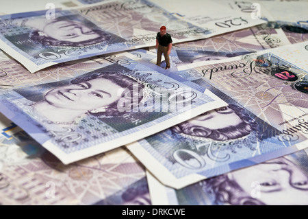 Miniature figure standing on a pile of twenty pound banknotes - Stock Photo