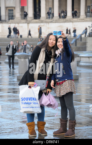 London, England, UK. Two Japanese tourists taking a selfie in Trafalgar Square, National Gallery behind - Stock Photo