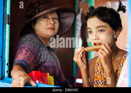 Girl and her mother riding a train in Yangon, Myanmar - Stock Photo