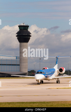 BMI Embraer taxis past control tower for take off at Manchester Airport - Stock Photo