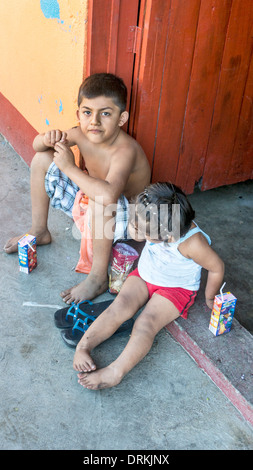 barefoot local Mexican children, small boy with defiant resigned face & his little sister sit on door stoop with - Stock Photo