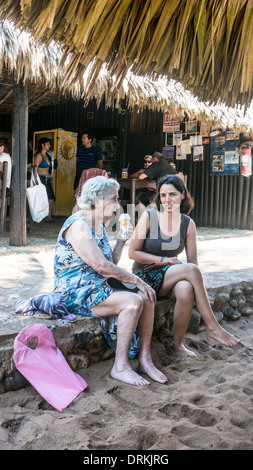 old woman eating ice cream & gossiping with young woman relative sitting on curb of terrace at popular beachfront - Stock Photo