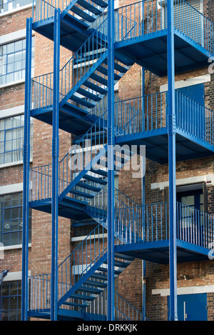 Blue external fire escape staircase on contemporary workspace in Victorian brick former warehouse at Highgate Studios - Stock Photo