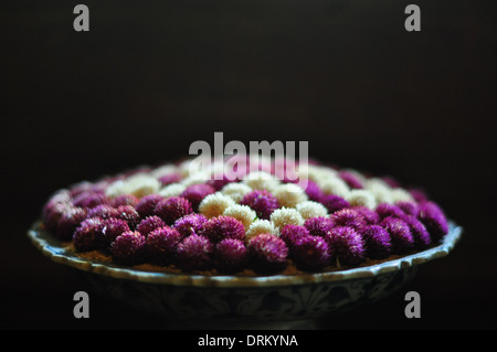 Globe amaranth (gomphrena globosa, or 'bachelor button') flowers in a Thai floral arrangement. - Stock Photo