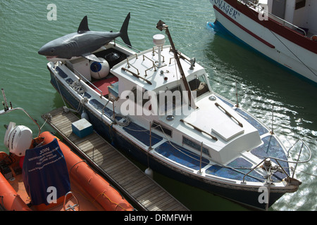 Fishing boat with a large plastic shark on the back in Brighton Marina, UK - Stock Photo