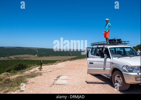 Boy standing on a car roof rack overlooking the landscape of Addo Elephant National Park, Eastern Cape, South Africa - Stock Photo