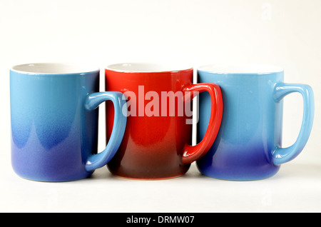 three colorful coffee mugs (blue, red) on a white background - Stock Photo