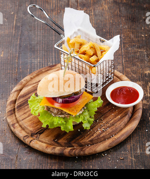 Burger and French fries in basket on wooden background - Stock Photo