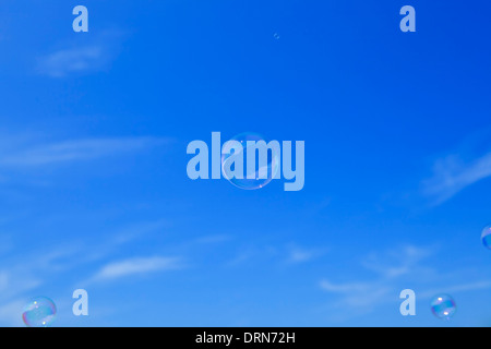 Soap bubbles floating in the blue sky - Stock Photo