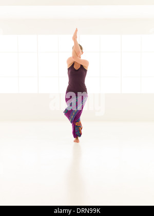 young woman sitting in difficutl yoga pose full frontal