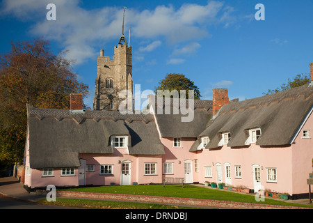 The Pink Cottages beneath St Mary's church, Cavendish, Suffolk, England. - Stock Photo