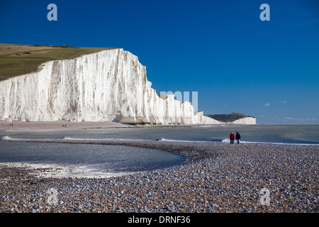 Couple walking beneath the Seven Sisters, Cuckmere Haven Beach, County Sussex, England. - Stock Photo