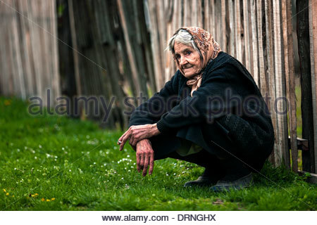 An old woman sitting in front of a wooden fence. - Stock Photo