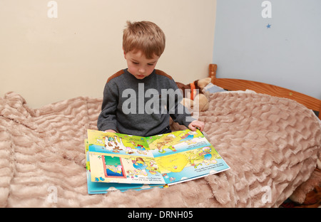 Boy Looking At Picture Book On The Floor Stock Photo